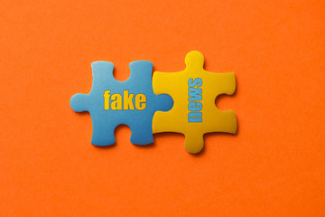 Wall Mural - Two colored details of puzzle with text fake news on orange background, Yellow and Blue, close up