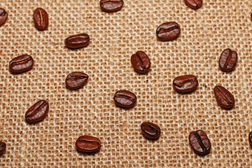 Grains of fried delicious and fragrant coffee on sack cloth.