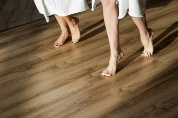 Closeup shot of female legs. Two young women in bathrobes