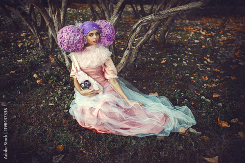 Beautiful model wearing pink dress is posing in a creative wig