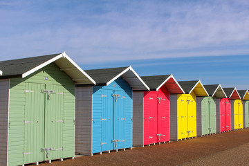 a row of colourful beach huts, against a blue sky