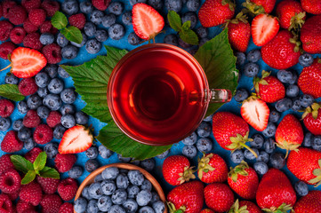 Cup of herbal tea with berries mix of strawberry, blueberry, raspberry and spices. Healthy summer drink. Top view