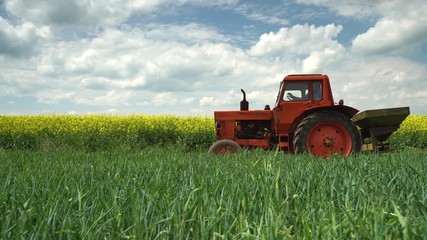 Wall Mural - Tractor in the agricultural fields and dramatic clouds