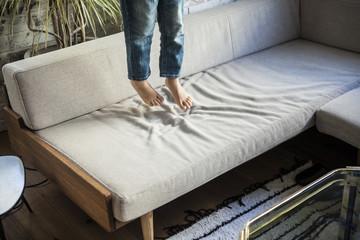 ソファーで飛び跳ねる女の子。足。