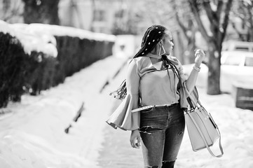 Rich african american girl with dreads and handbag at sunny winter day. Black stylish woman.