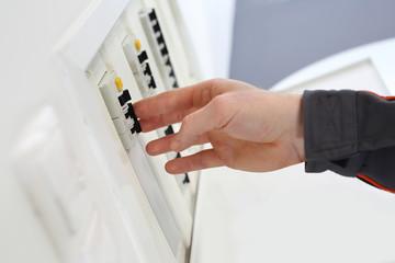 Mężczyzna przełącza wyłączniki nadprądowe w domowej skrzynce elektrycznej