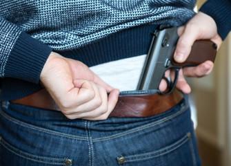 Man hiding gun behind his back.