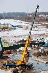 Crane beam machinery and bulldozer on building construction site on background of dirty ground. Industrial landscape with cranes and building, and working machinery