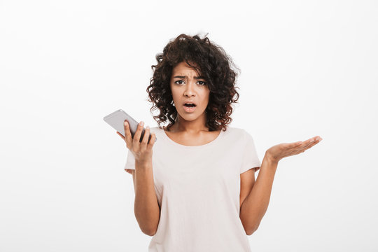 Portrait of confused puzzled woman with afro hairstyle wearing t-shirt holding cell phone and expressing misunderstanding, isolated over white background