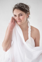 photo portrait of a girl with jewelery in her hair holding a white drapery
