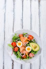 Smoked salmon salad with greens, tomatoes, eggs and avocado
