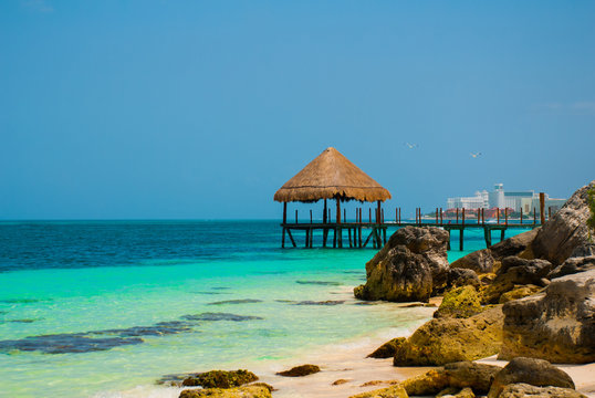 Pier and wooden gazebo by the beach. Tropical landscape with Jetty: sea, sand, rocks, waves, turquoise water. Mexico, Cancun