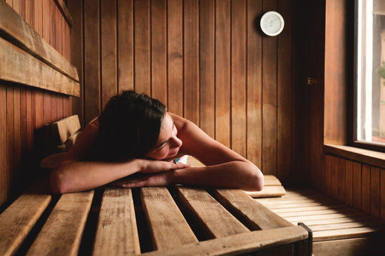 A beautiful woman wearing a white towel takes a sauna: The sauna is made of wood with a large window with a view of the snow. Concept of: relax, vacation, wellness center.