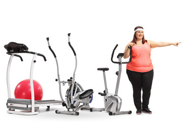 Overweight woman standing by exercise machines and pointing