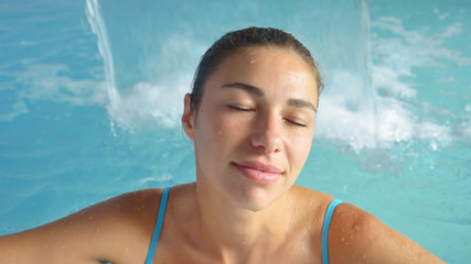 Beautiful young girl (woman) relaxed in a spa, in a blue bathing suit, on a blue background. Concept: spa procedures, body massages, spa cream, relax, spa water treatments, swimming pool