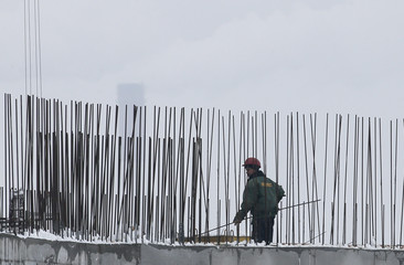 A worker holds a steel bar at a construction site in Kiev