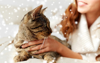 Fototapete - pets, animals, winter and people concept - close up of cat and woman in bed over snow