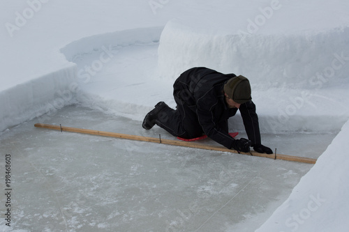 Ice maker marks area for an ice swimming pool on a frozen lake  Step