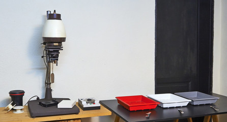 Photo enlarger and accessories in darkroom