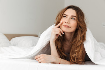 Portrait of smiling woman 20s lying in bed under white blanket in bedroom, and daydreaming or thinking looking upward