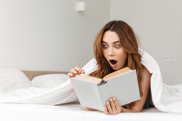 Portrait of shocked woman lying in bed under white blanket in bedroom, and reading captivating book