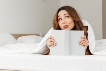 Portrait of romantic woman resting in bed under white blanket in bedroom, and reading fascinating book