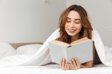 Portrait of joyous woman lying in bed under white blanket in bedroom, and reading interesting book