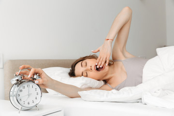 Portrait of young woman waking up in bed with white linen, yawning and touching ringing alarm clock