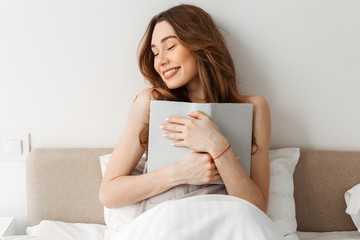 Portrait of beautiful smiling woman resting in comfortable bed after sleep in morning, and holding book in pleasure and happiness