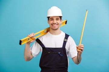 Fototapeta Happy male builder in protective helmet holding level tool obraz