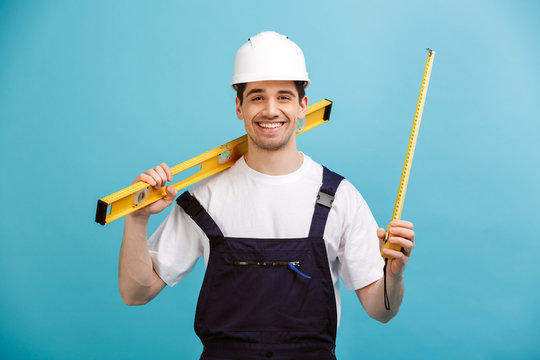 Happy male builder in protective helmet holding level tool