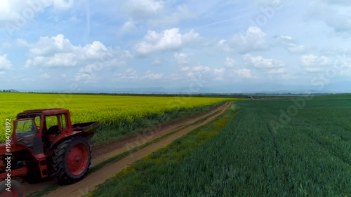 Wall mural Tractor in the agricultural fields and dramatic clouds