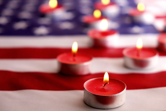 Mourning candles burning on USA American national flag background. Memorial weekend, patriot veterans day, 9/11 National Day of Service & Remembrance. Moment of silence concept. Close up, copy space.