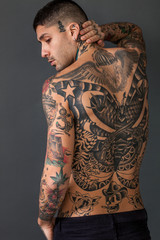 Handsome man back portrait with tattoos all over his body