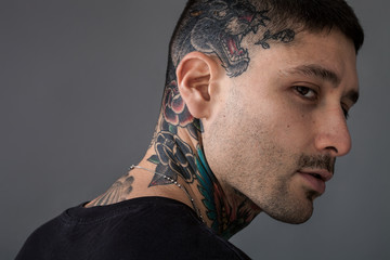 Handsome man with tiger and roses tattooed on neck and head