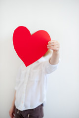 Red heart in girl's hands on the white background