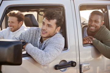 Three young adult male friends going on vacation in a car