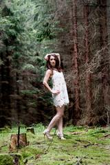 attraktive dunkelhaarige frau im kleid sitz  / Steht im Wald