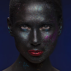 Vogue style portrait of a woman. Black and blue makeup with glitter and red lips. Dark background. Facial make up art concept