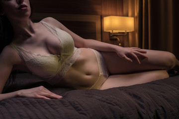 Beautiful young girl in sexy light underwear in a dark room on the bed