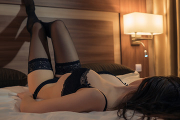 Charming girl posing on bed in sexy black lingerie and stockings