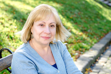 Middle-aged blond woman sitting on a  bench in the park looking at the camera on the autumn spring background. Portrait of beautiful senior happy elderly blond woman in a park on a sunny day.