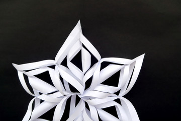 White snowflake 3d cutout on black background made from paper cut to decorative.