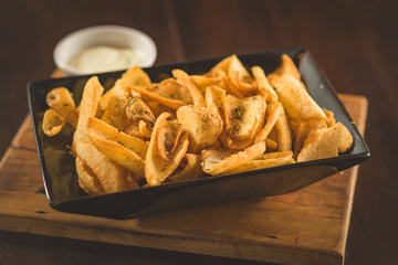 Rustic fries served on a square plate in black color