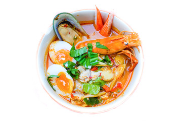 Thai noodle soup (Tom Yum Soup Recipe) with shrimp, dumpling fish, New Zealand mussels, crab and egg (onsen tamago) serve on white bowl for Thai food background or texture.