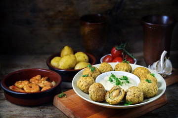 spanish tapas appetizers such as baked olives, prawn shrimps, potatoes, tomato and garlic sauce on a dark rustic wooden background, copy space