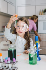 Little girl doing some science, playing in the kitchen
