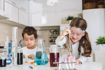Children playing in the kitchen , with water and colors doing some science