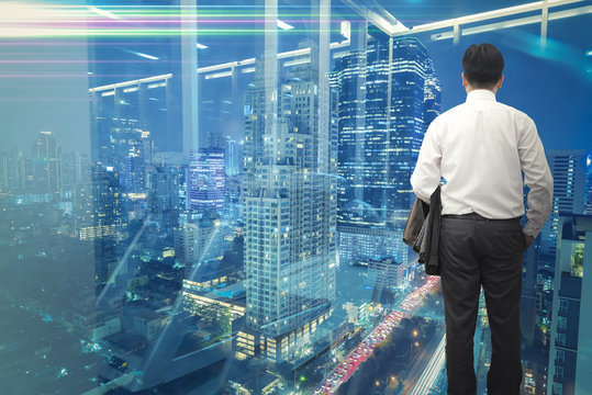 Business vision concept. Backside businessman standing and looking out to modern business district city at night.
