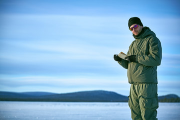Young man in military clothes is makes notes in a paper notebook against a blue sky with clouds